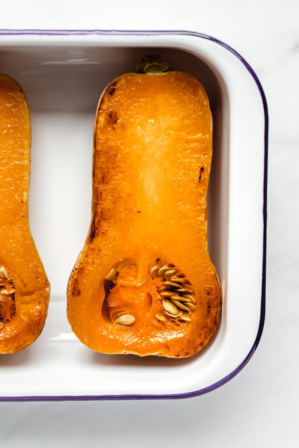 a roasted butternut squash in a white pan