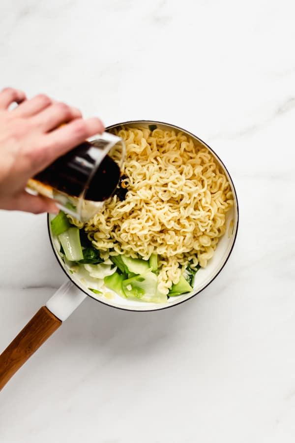 a hand pouring sauce onto ramen noodles in a white pot