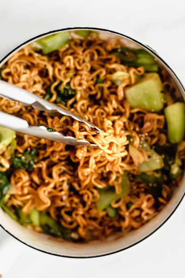 Tongs scooping up ramen noodle stir fry