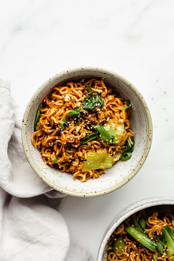 two bowls of ramen noodles topped with green onions and sesame seeds