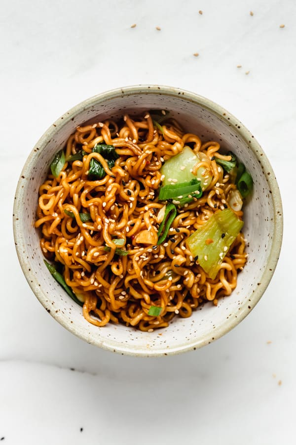 Ramen noodle stir fry in a blue ceramic bowl topped with sesame seeds