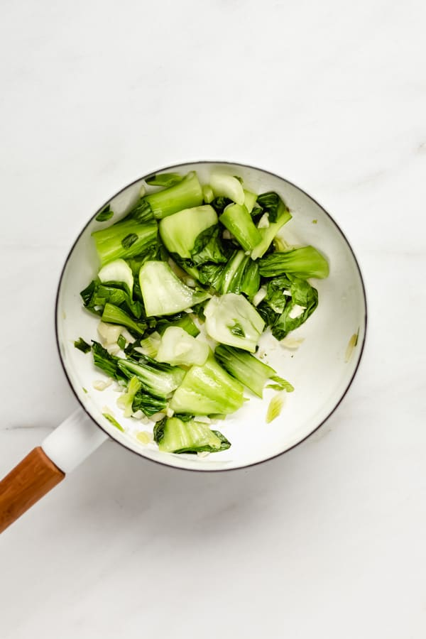 Bok choy chopped up in a white pot