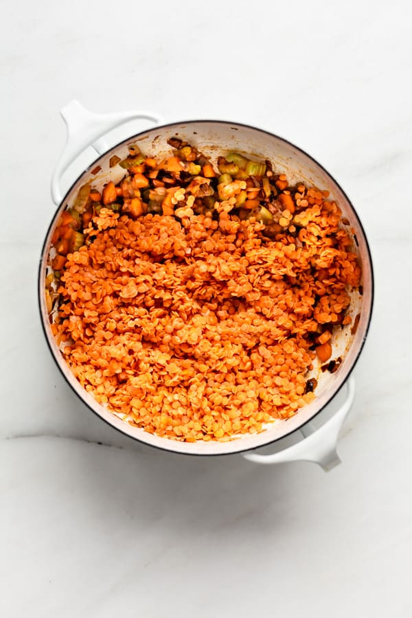 A white pot filled with vegetables and red lentils