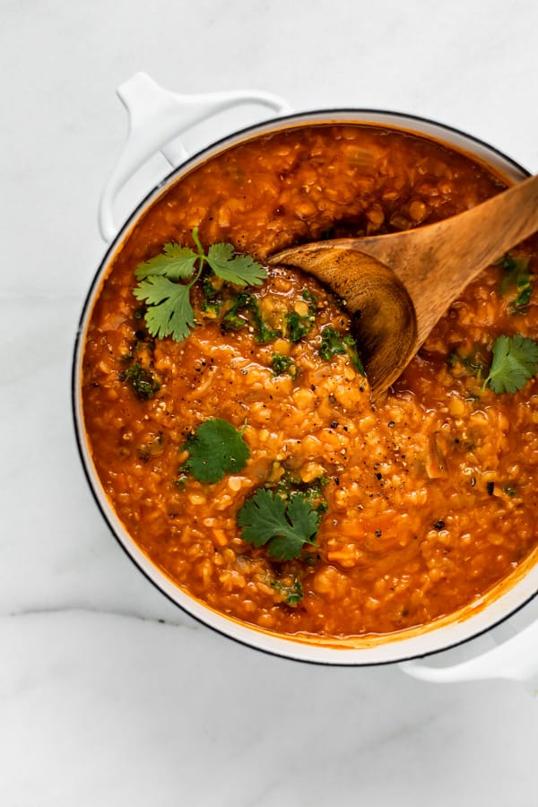 A white pot filled with red lentil curry