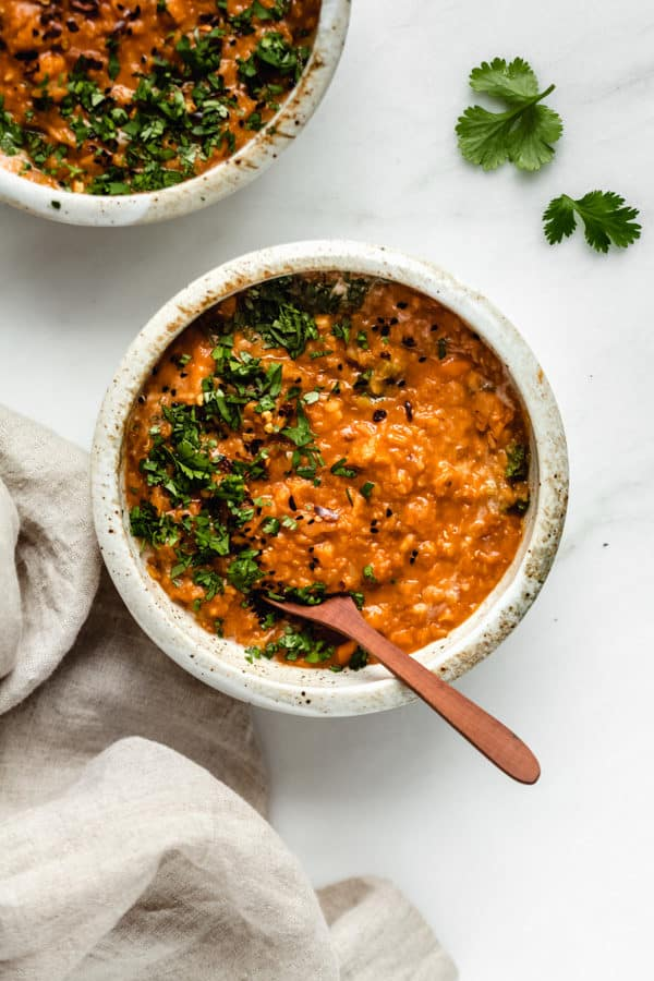 Red lentil curry in a white ceramic bowl with a linen napkin on the side