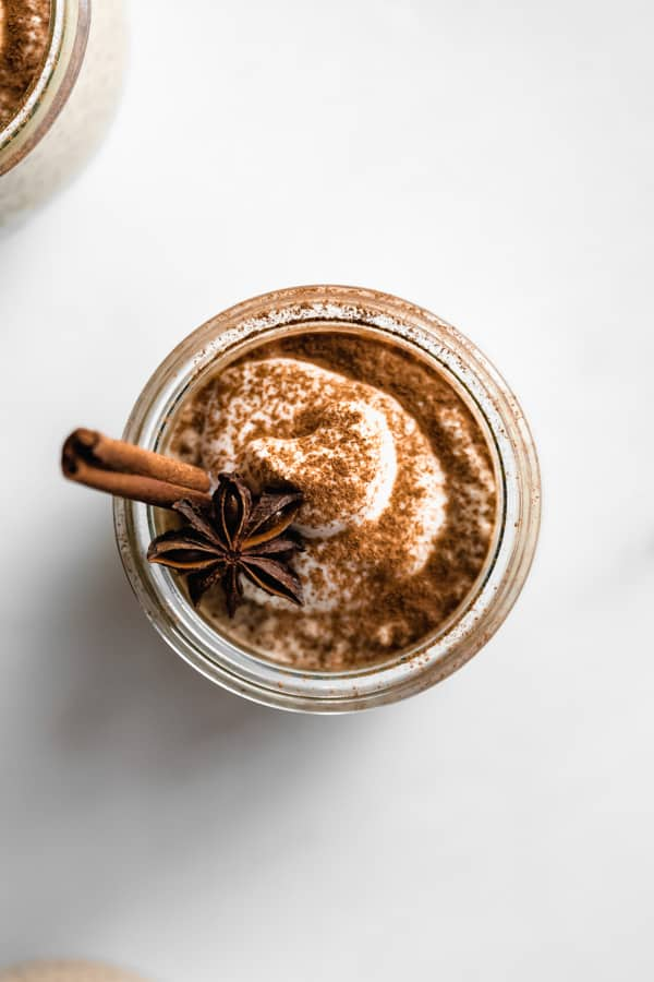 a top down view of a chai latte chia pudding cup topped with cinnamon and star anis