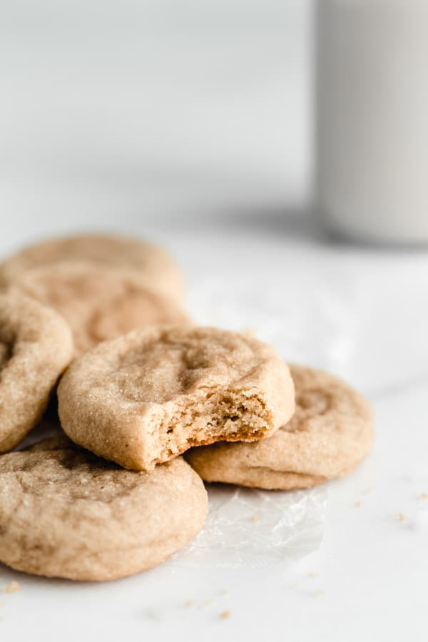 a pile of snickerdoodle cookies on a piece of parchment paper
