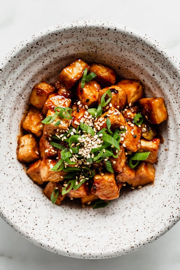 A bowl of General Tso Tofu topped with green onions and sesame seeds