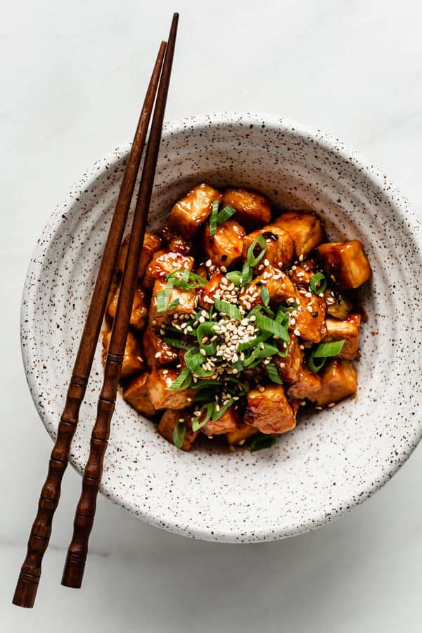 General Tso Tofu in a speckled ceramic bowl with wooden chopsticks on the side