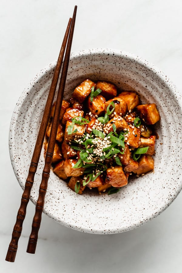 General Tso's Tofu in a white speckled bowl with chopsticks on the side