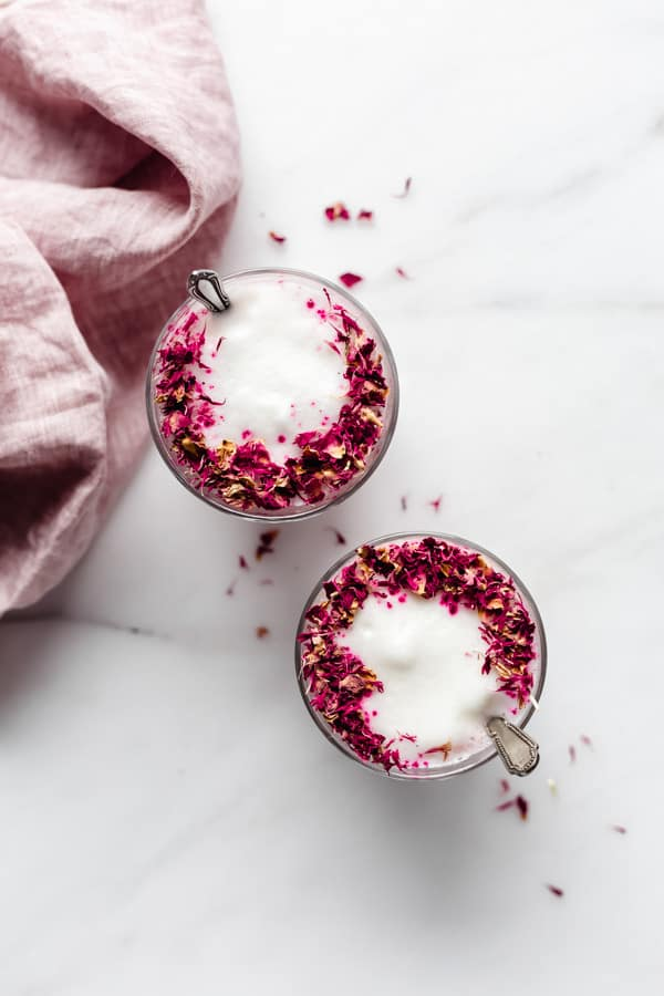 two glasses of hibiscus rose lattes topped with rose petals