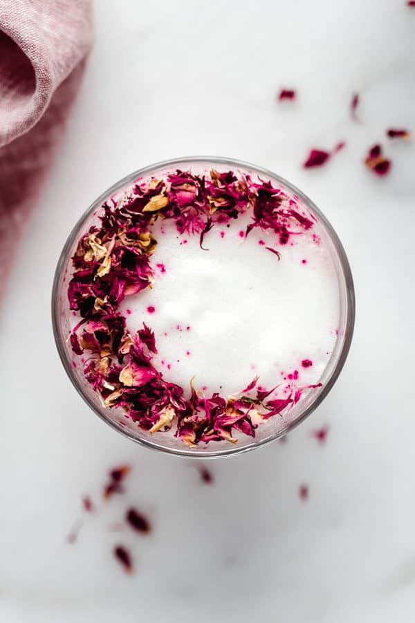 a hibiscus rose latte topped with rose petals