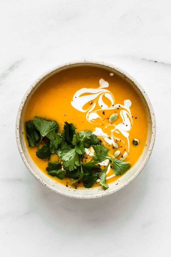 a bowl of butternut squash soup topped with cilantro, coconut milk and pumpkin seeds