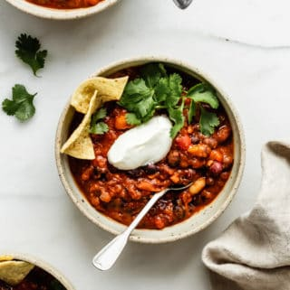three bowls of vegan chili topped with vegan sour creme, cilantro and tortilla chips