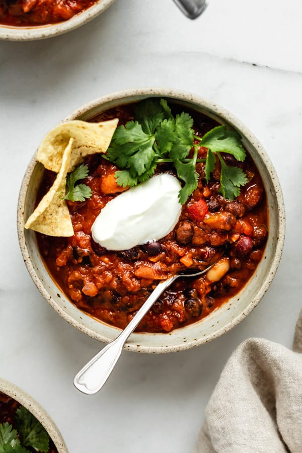a bowl of vegan chili with a spoon in it topped with vegan sour cream