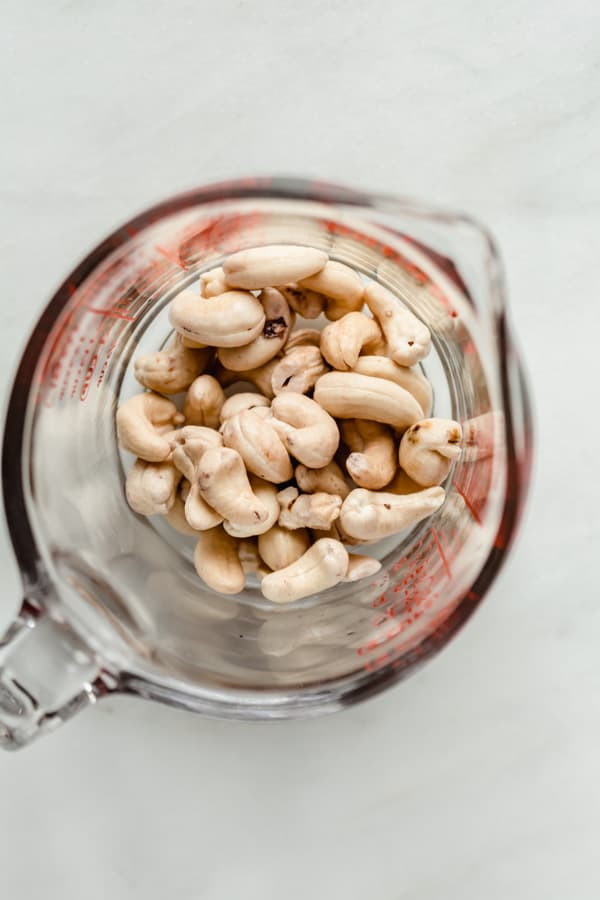 a measuring cup with raw cashews in it