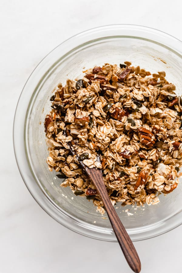 a clear mixing bowl with un-baked tahini granola in it