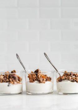 three cups of yogurt topped with orange cardamom tahini granola