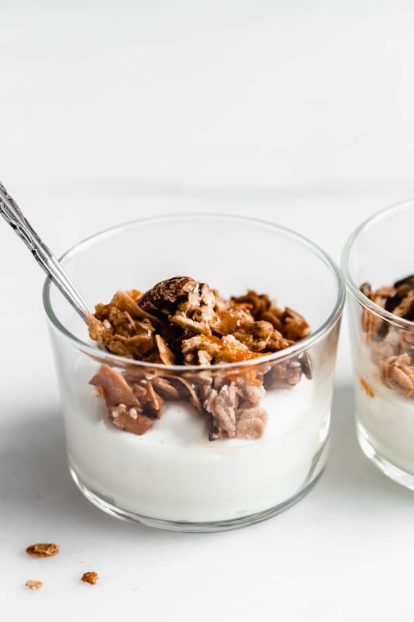 a cup of yogurt topped with orange cardamom tahini granola and orange zest