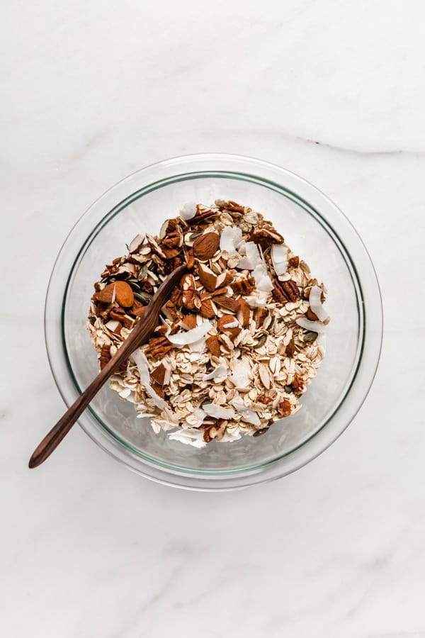 a clear mixing bowl filled with oats, coconut and nuts