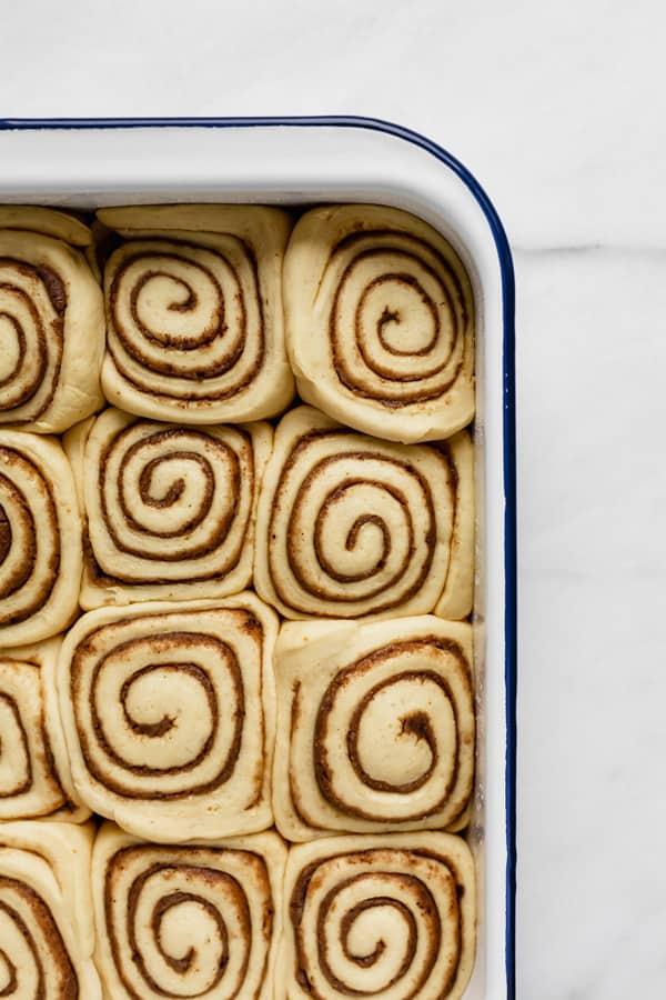 a white enamel baking pan with unbaked cinnamon rolls in it