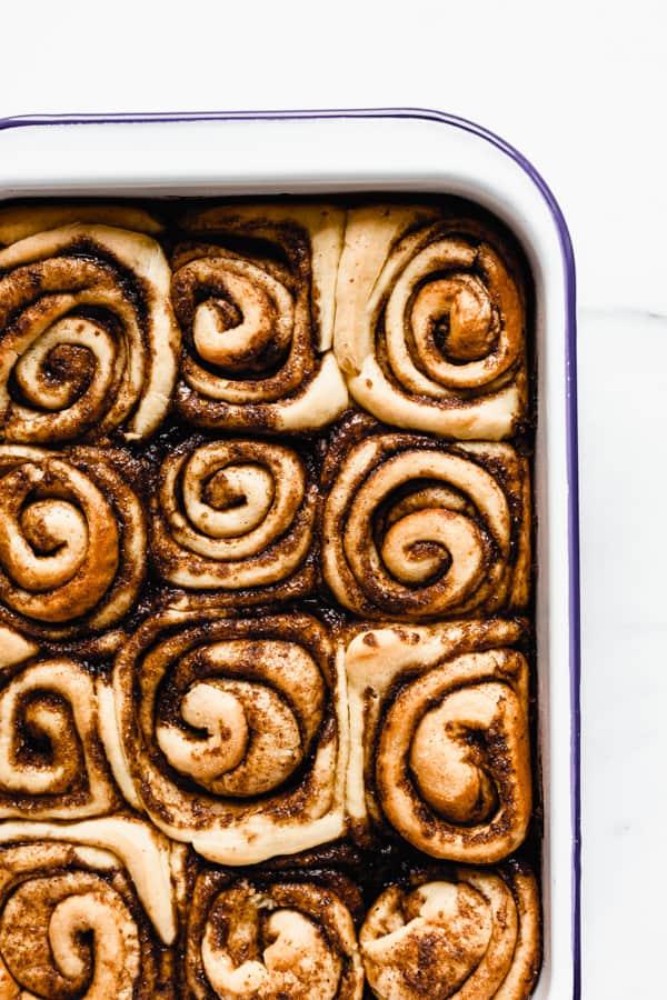 a white enamel baking pan with baked cinnamon rolls in it