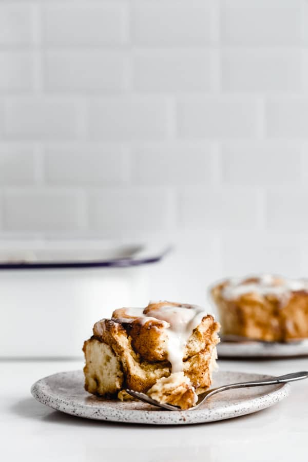 a cinnamon roll on a plate with a white pan in the background