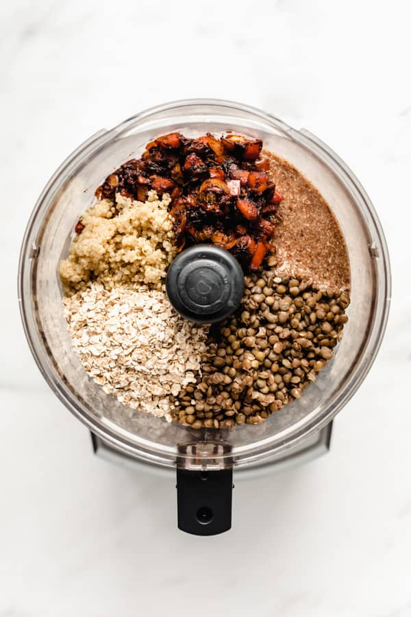 A food processor with veggies, lentils, flax oats and quinoa in it