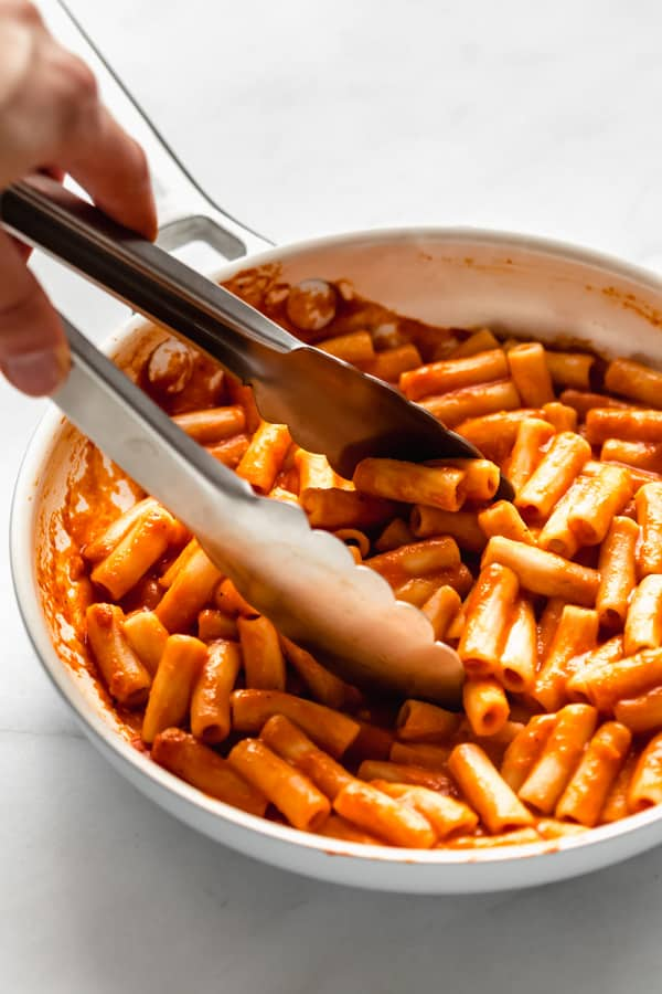 tongs scooping up roasted red pepper pasta from a pan