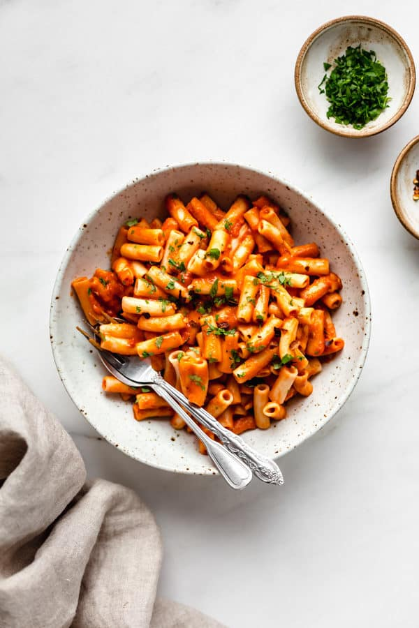roasted red pepper pasta in a white speckled pasta bowl with a side of parsley