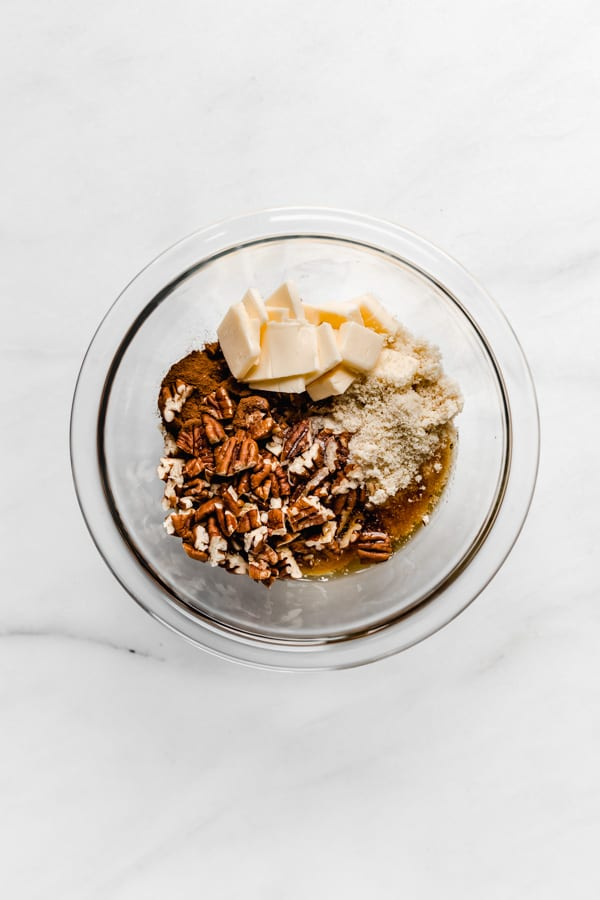 a clear mixing bowl with pecans, almond flour, vegan butter and maple syrup