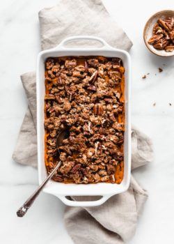 vegan sweet potato casserole in a white baking dish and a serving spoon in it