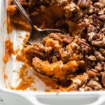 a serving spoon scooping up some vegan sweet potato casserole out of a baking dish