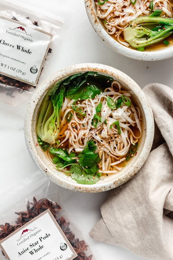 A bowl of Pho soup with packs of spices and a napkin on the side