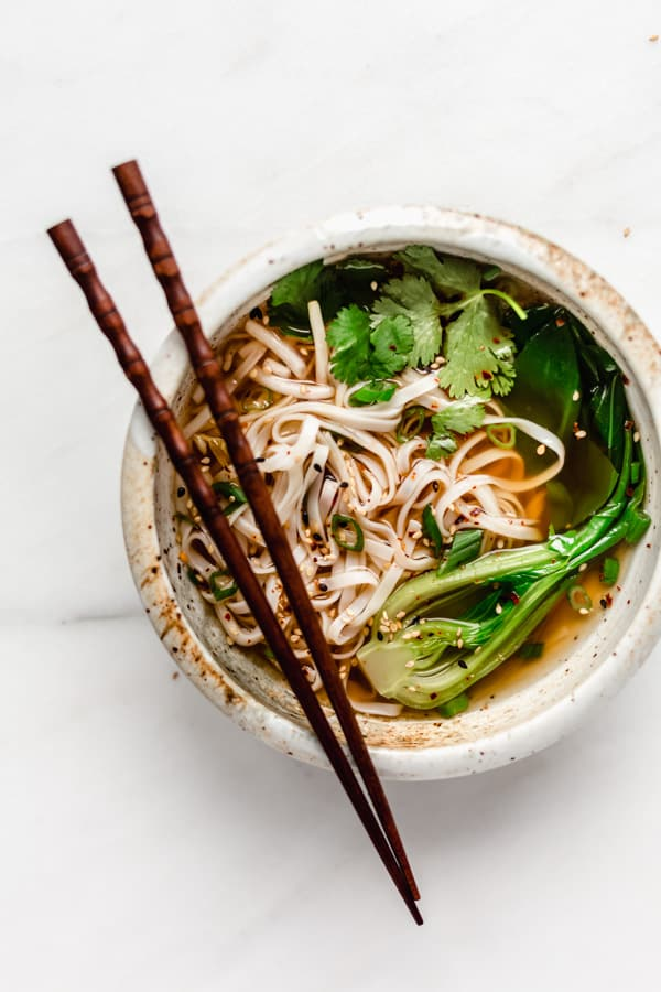 A bowl of pho soup with noodles and bok choy in it