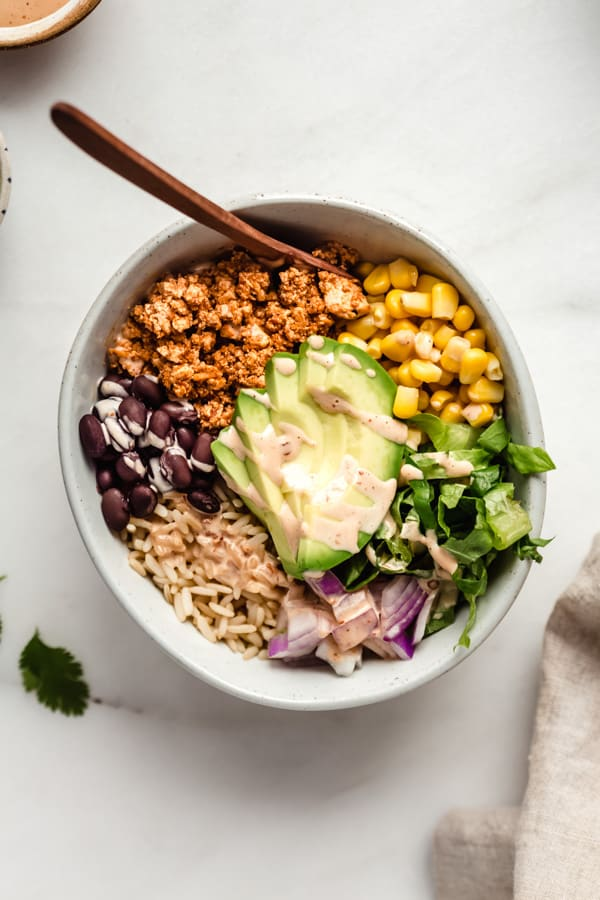 A bowl of chipotle sofrtias with avocado, rice, beans, corn and lettuce