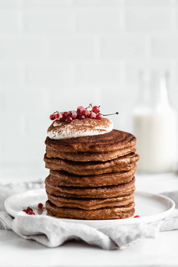 a stack of gingerbread pancakes topped with yogurt and currants
