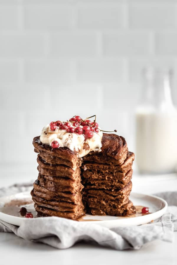 stacked gingerbread pancakes with a slice cut out of them