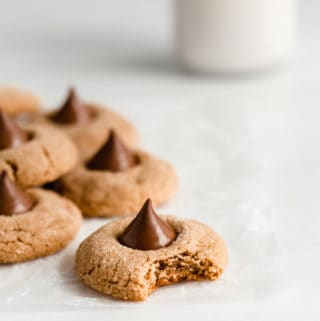 peanut butter blossom cookies on parchment paper with a jug of milk in the back