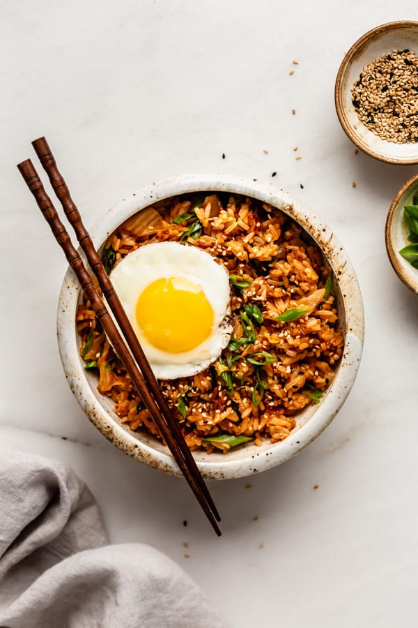 Kimchi fried rice in a white bowl topped with an egg and sesame seeds in a small bowl on the side