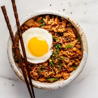 A bowl of kimchi fried rice topped with an egg and chopsticks on top