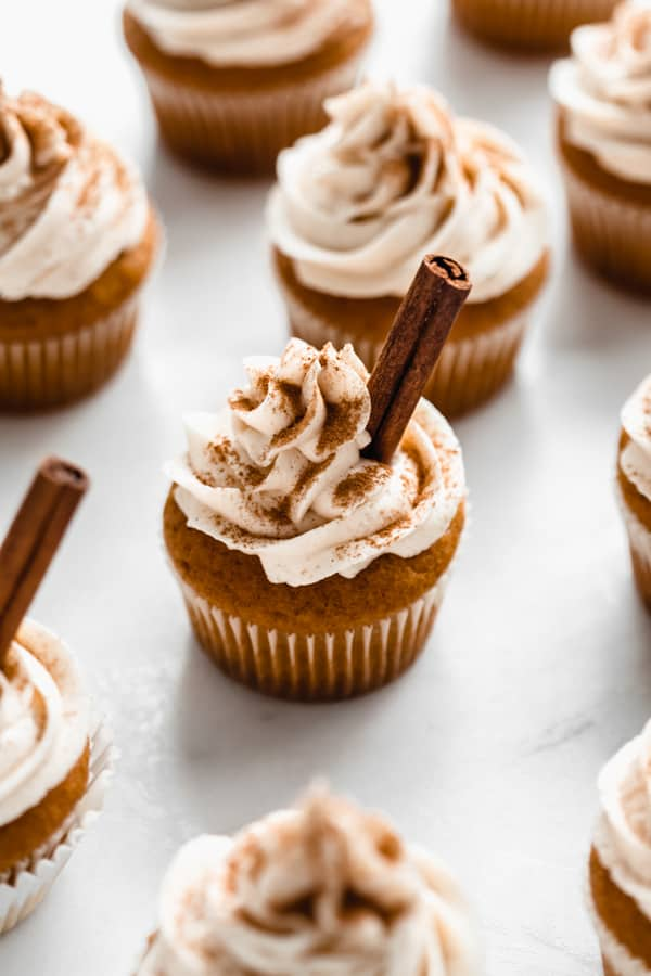 pumpkin spice latte cupcakes topped with frosting and cinnamon sticks