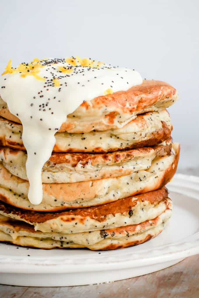 healthy breakfast plate of lemon poppyseed pancakes topped with white yogurt, poppyseeds, and lemon zest
