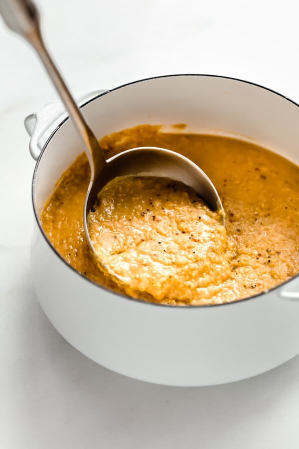 a ladle scooping up red lentil dal out of a white pot