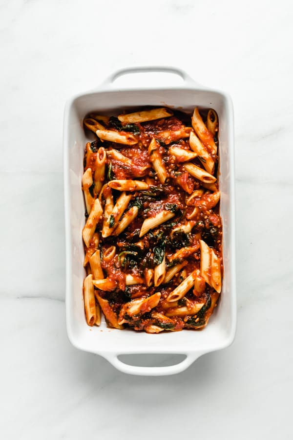 a baking dish with penne and sauce in it
