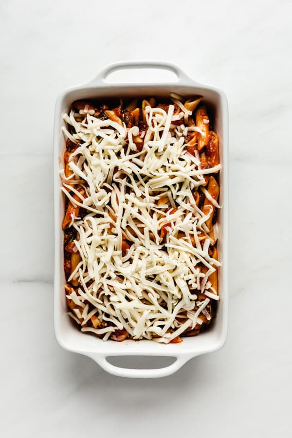 a baking dish with unbaked baked ziti in it