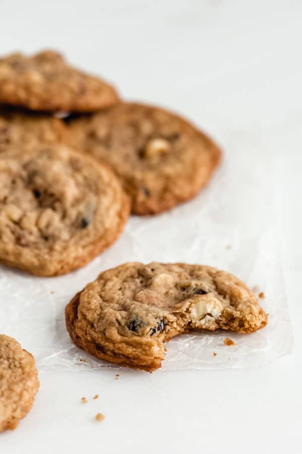 a chewy white chocolate cranberry cookie on some parchment paper with a bite taken out of it