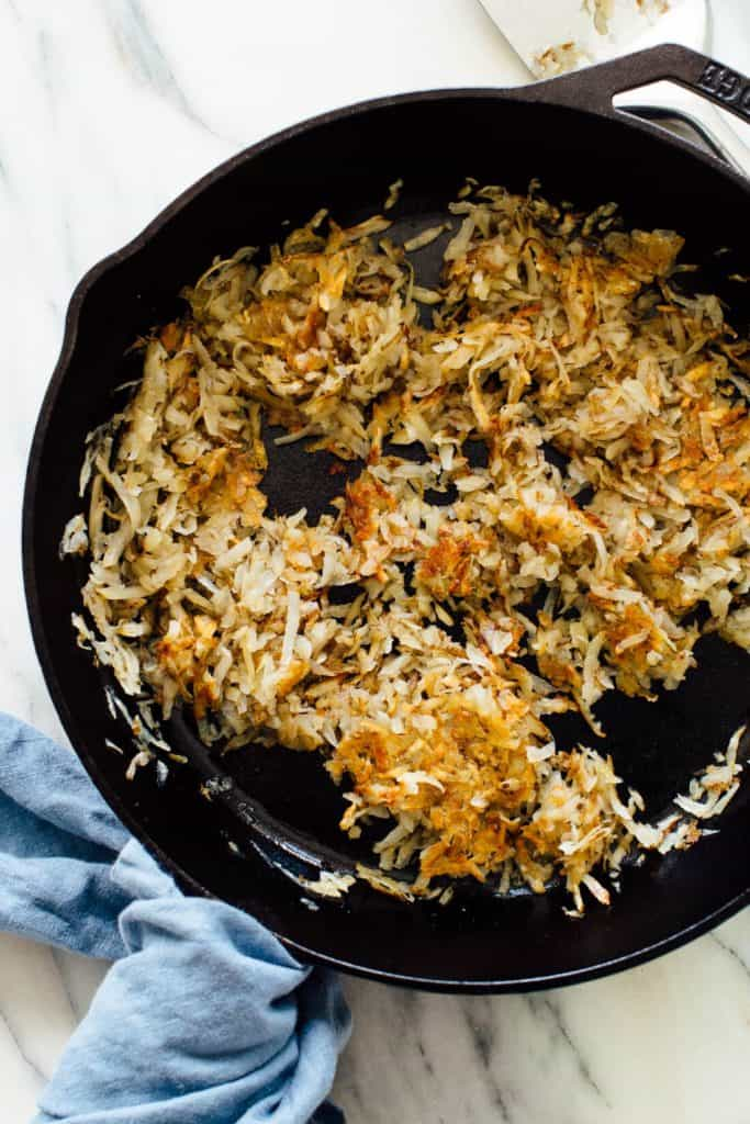shredded hash browns being cooked in a cast iron skillet