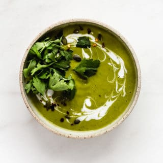 a bowl of broccoli soup topped with coconut milk and parsley