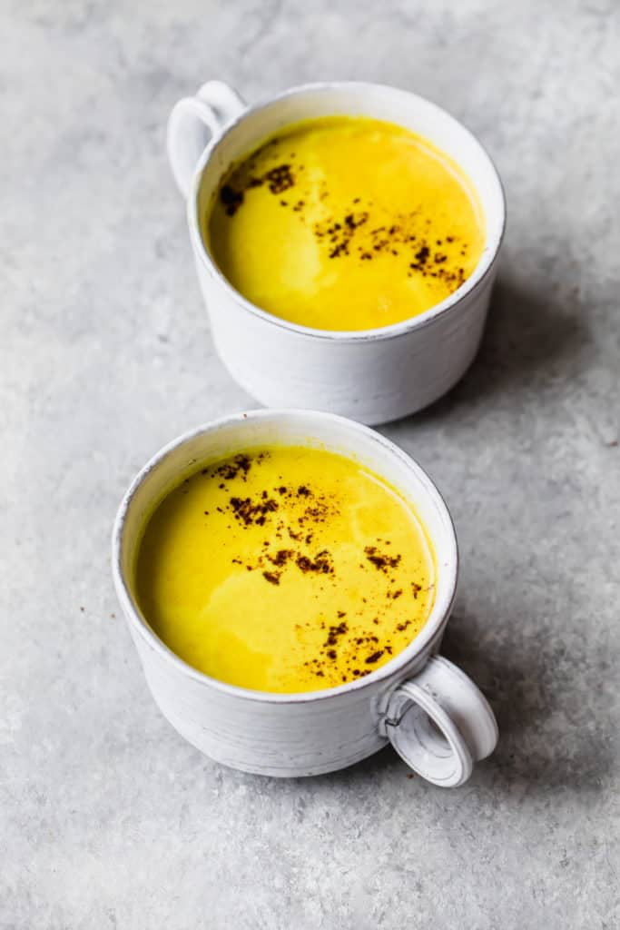 two white mugs filled with yellow turmeric latte and topped with cinnamon, on a grey background